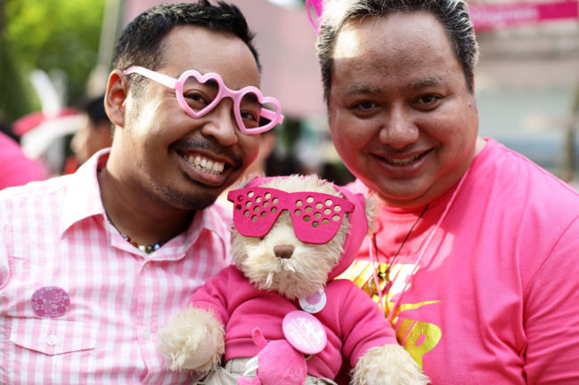SINGAPORE - JUNE 30: Participants dress in various shades of pink pose for a photo during the 'Night Pink Dot' event arrange to increase awareness and understanding of the lesbian, gay, bisexual and transgender community in Singapore at Hong Lim Park on June 30, 2012 in Singapore. The event is the fourth annual gathering held in support of the freedom to love. (Photo by Suhaimi Abdullah/Getty Images)