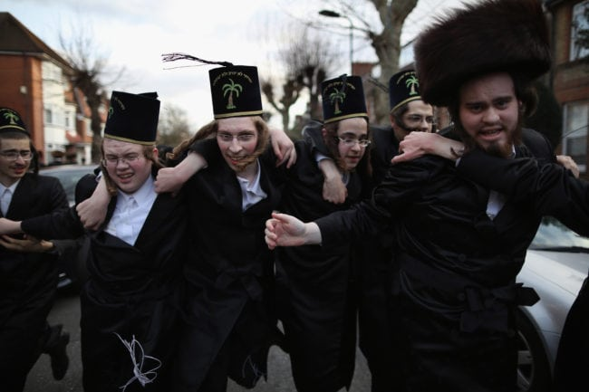 LONDON, ENGLAND - MARCH 05: A group of Orthodox Jewish boys dance in the street before going into the home of a local businessmen while collecting money during the Jewish holiday of Purim on March 5, 2015 in London, England. The annual Purim holiday is celebrated by Jewish communities around the world with parades and costume parties. The Biblical Book of Esther recorded the deliverance of the Jewish people from a plot to exterminate them in the ancient Persian empire 2,500 years ago and continues to be celebrated today. (Photo by Dan Kitwood/Getty Images)