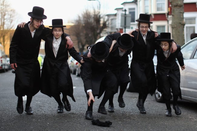 LONDON, ENGLAND - MARCH 05: A group of Orthodox Jewish boys dance in the street before going into the home of a local businessmen while collecting money for their school during the Jewish holiday of Purim on March 5, 2015 in London, England. The annual Purim holiday is celebrated by Jewish communities around the world with parades and costume parties. The Biblical Book of Esther recorded the deliverance of the Jewish people from a plot to exterminate them in the ancient Persian empire 2,500 years ago and continues to be celebrated today. (Photo by Dan Kitwood/Getty Images)