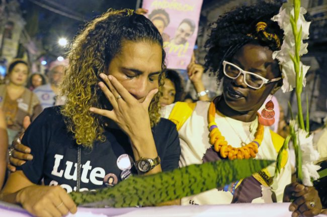 Anielle Silva (L), sister of activist Marielle Franco, cries at a memorial in Rio de Janeiro on April 14, 2018, one month after her murder in Lapa. The murder of Franco, a black Brazilian activist who fought her way out of the slums to become a popular councilor, made headlines around the world. The outspoken 38-year-old, who was a critic of police brutality, an advocate for minorities and the posterchild of a new type of politics, was shot dead on March 14 in an assassination-style killing with four bullets to the head.   / AFP PHOTO / DIEGO HERCULANO        (Photo credit should read DIEGO HERCULANO/AFP/Getty Images)