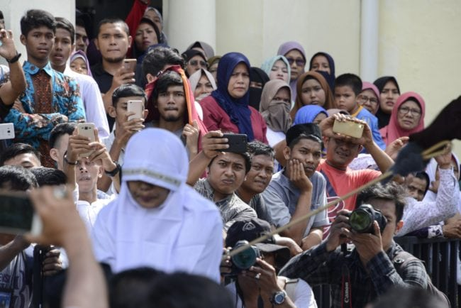 TOPSHOT - EDITORS NOTE: Graphic content / Onlookers watch as a member of Indonesia's Sharia police (at R-outside frame) whips a non-Muslim woman (bottom L) for trading alcohol during a public caning ceremony outside a mosque in Banda Aceh, the capital of Aceh province on July 13, 2018. - A gay couple was also publicly whipped in Indonesia's conservative Aceh province on July 13, despite an earlier pledge by officials to stop the punishment after it drew international criticism. (Photo by CHAIDEER MAHYUDDIN / AFP) (Photo credit should read CHAIDEER MAHYUDDIN/AFP/Getty Images)