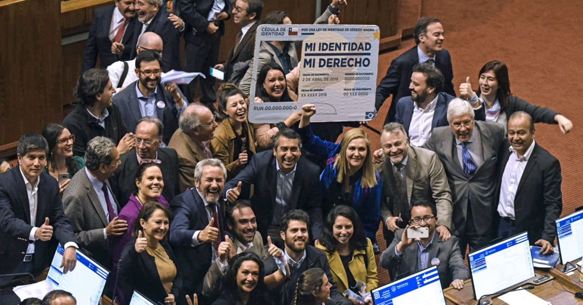 "Chilean deputies for the Frente Amplio party, celebrate as they hold a giant fake Chilean Identity card reading ""My identity, my right"", after voting a gender identity law, during a session at the Deputies Charmber, of the National Congress in Valparaiso, Chile, on September 12, 2018. (Francesco Degasperi/AFP/Getty)"