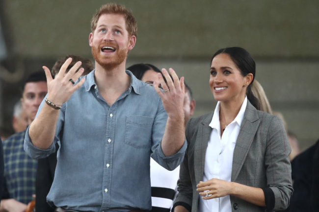 DUBBO, AUSTRALIA - OCTOBER 17: Prince Harry, Duke of Sussex and Meghan, Duchess of Sussex react as they look out towards the heavy rain and storm as they visit the Clontarf Foundation and Girls Academy at Dubbo College on October 17, 2018 in Dubbo, Australia. The Duke and Duchess of Sussex are on their official 16-day Autumn tour visiting cities in Australia, Fiji, Tonga and New Zealand. (Photo by Cameron Spencer/Getty Images)