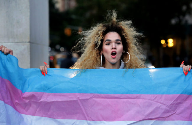 """NEW YORK, NY - OCTOBER 21: Morgin Dupont, 25, a woman of trans experience, holds up the flag for Transgender and Gender Noncomforming people at a rally for LGBTQI+ rights at Washington Square Park on October 21, 2018 in New York City. Based on a leaked memo, The New York Times had reported that morning that the Trump administration is considering re-defining gender as a """"biological, immutable condition determined by genitalia at birth,"""" which activists say would subject transgender and gender nonconforming people to discrimination, harassment, and violence. (Photo by Yana Paskova/Getty Images)"""