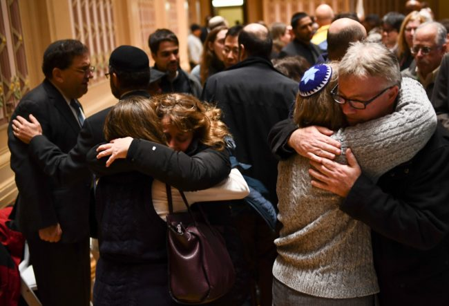 """People hug after a vigil, to remember the victims of the shooting at the Tree of Life synagogue the day before, at the Allegheny County Soldiers Memorial on October 28, 2018, in Pittsburgh, Pennsylvania. - A man suspected of bursting into a Pittsburgh synagogue during a baby-naming ceremony and gunning down 11 people has been charged with murder, in the deadliest anti-Semitic attack in recent US history. The suspect -- identified as a 46-year-old Robert Bowers -- reportedly yelled """"All Jews must die"""" as he sprayed bullets into the Tree of Life synagogue during Sabbath services on Saturday before exchanging fire with police, in an attack that also wounded six people. (Photo by Brendan Smialowski / AFP) (Photo credit should read BRENDAN SMIALOWSKI/AFP/Getty Images)"""