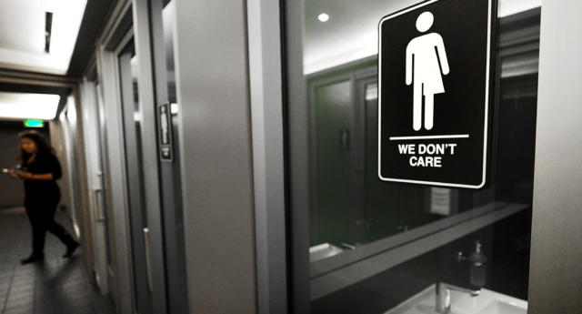 Gender neutral signs are posted in the 21C Museum Hotel public restrooms on May 10, 2016 in Durham, North Carolina during clashes over trans rights (Sara D. Davis/Getty)