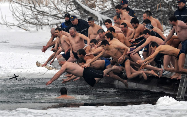 Bulgarians dive into icy water as they compete to catch a cross in the middle of a lake in Sofia on Epiphany Day on January 6, 2009. It is believed that the man who is the first to grab the cross, thrown into the water by an Eastern Orthodox priest, will be healthy throughout the new year.   AFP PHOTO / DIMITAR DILKOFF (Photo credit should read DIMITAR DILKOFF/AFP/Getty Images)