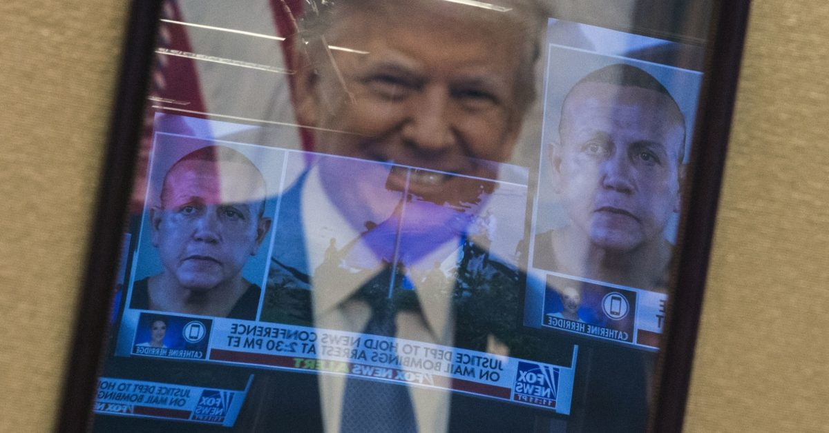 Mugshots of bombing suspect Cesar Sayoc are reflected on a portrait of US President Donald Trump prior to a press conference at the Department of Justice in Washington, DC on October 26, 2018. (Andrew Caballero-Reynolds/AFP/Getty)