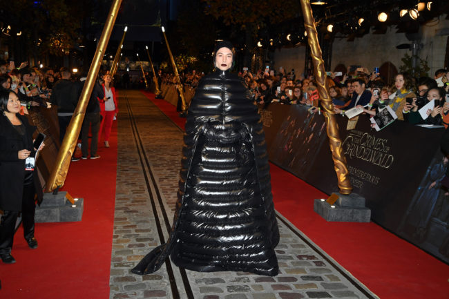 Ezra Miller walking into premiere in a black, shiny outfit