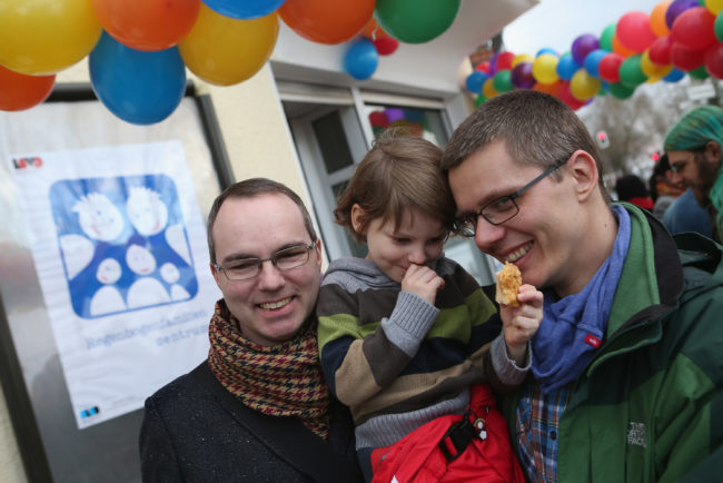 Gay couple hug their daughter at the opening of Germany's first gay parenting counseling centre.