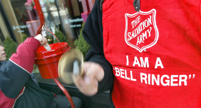 A donation is made as a Salvation Army bell ringer works outside a store (Tim Boyle/Getty)