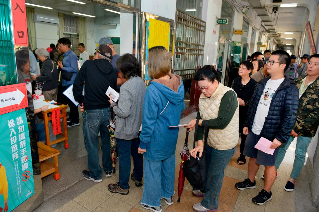 Residents queue outside a polling station at an elementary school on November 24, 2018. (CHRIS STOWERS/AFP/Getty)