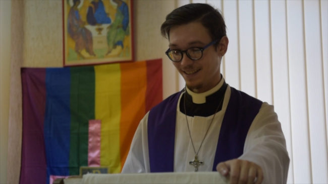 Openly gay priest Aleksandr recites prayers in church