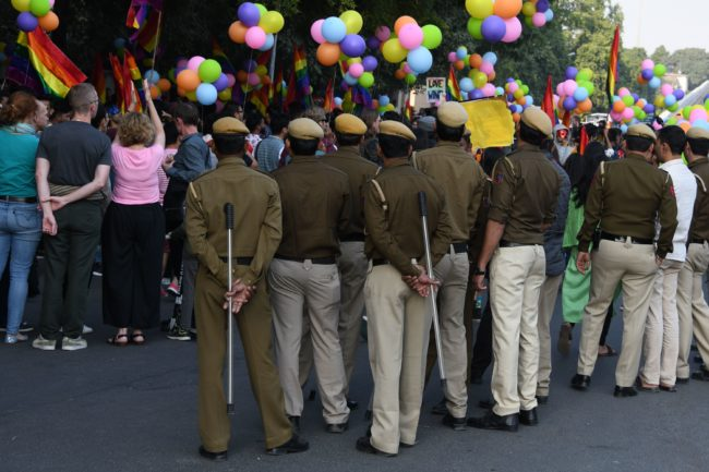 Police keep watch as Indian members and supporters of the LGBT community march