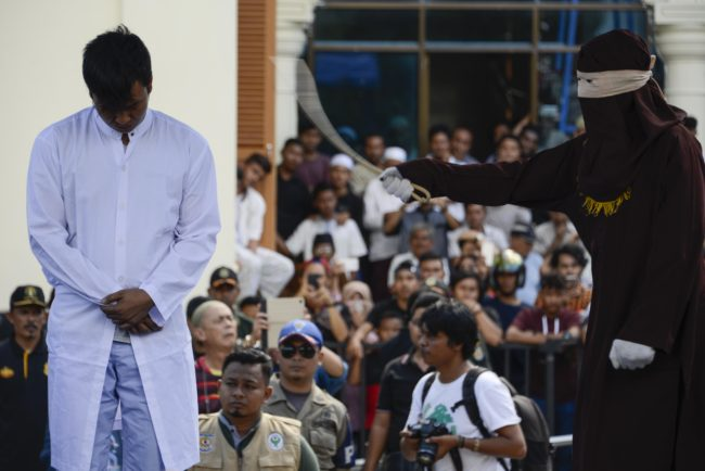 A member of Indonesia's Sharia police (R) whips a man (L) accused of having gay sex during a public caning ceremony outside a mosque in Banda Aceh