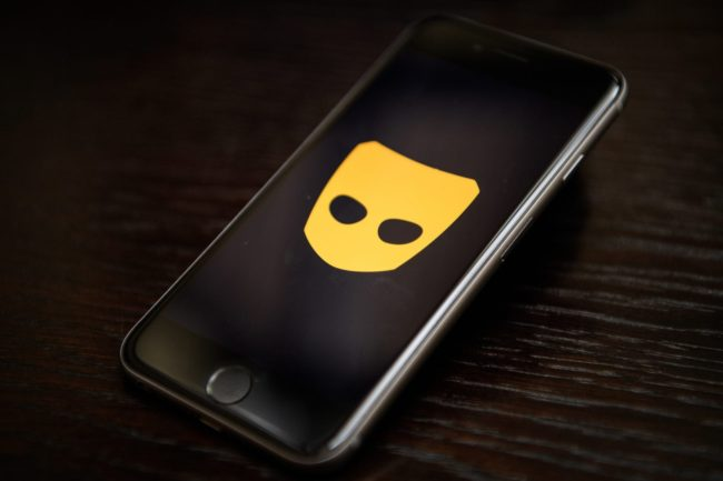 A phone displays the logo of gay hook-up app Grindr