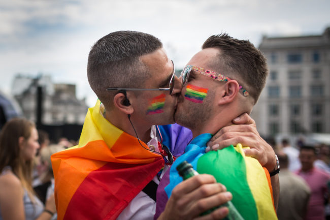 A gay couple kiss in Trafalgar Square after the annual Pride in London Parade
