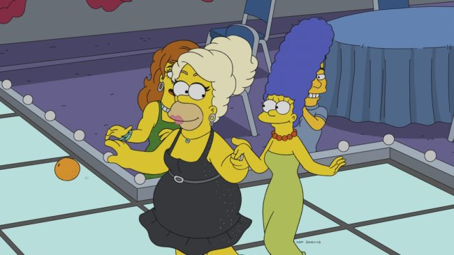 Homer Simpson walks down a catwalk in drag with Marge Simpson on The Simpsons