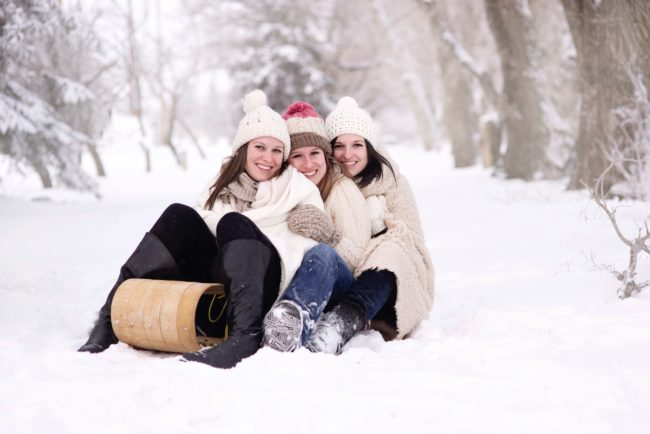 Three women get extremely close on a sleigh in the snow