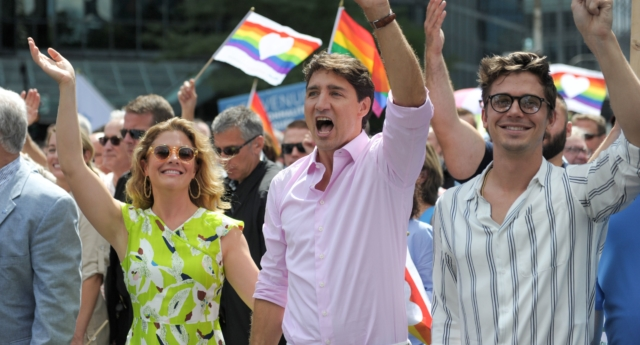 Canadian Prime minister Justin Trudeau, who has approved the new $1 coin design, leads the 2018 Montreal Pride parade along with his wife Sophie Gregoire Trudeau and Queer Eye star Antoni Porowski on August 19, 2018. (Eric Thomas/AFP/Getty)
