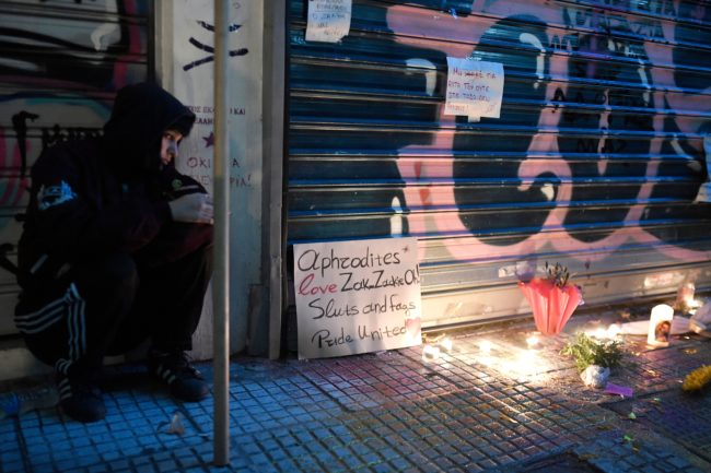 A girl sits by a makeshift memorial outside a jewellery shop where Zak Kostopoulos, a Greek militant homosexual was lynched on September 21.