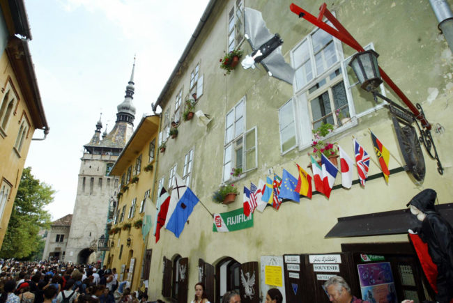A Dracula-like puppet flight over the people in front of a souvenirs store in Sighisoara, where the viral gay love story is set.