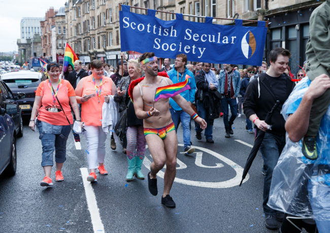 A participant wears rainbow pants and waves a flag during the Glasgow Pride.