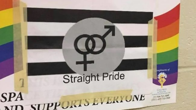 A 'Straight Pride' flag is plastered over the top of a Gay-Straight Alliance poster at the Canada school