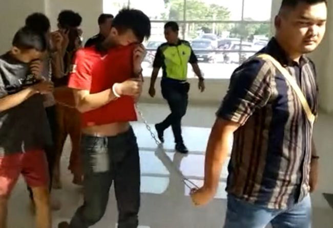 Four people charged with a trans woman's murder are led through the Magistrate's Court in Selangor, Malaysia