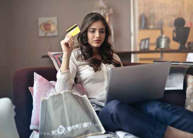 A woman uses her laptop while holding a credit card