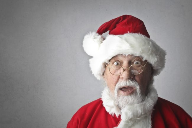 An older man dressed as Santa, with a shocked expression