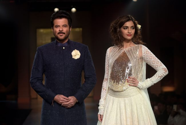Indian Bollywood actors Anil Kapoor and daughter Sonam Kapoor model creations by designer Manish Malhotra during a charity fashion show in Mumbai on April 4, 2015