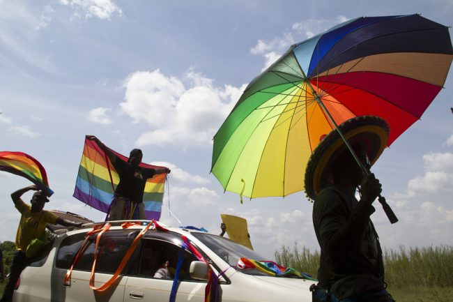 A person holds an umbrella bearing the colors of the rainbow flag as others wave flags during the the first gay pride rally since the overturning of a tough anti-homosexuality law, which authorities have appealed, in Entebbe, on August 9, 2014.