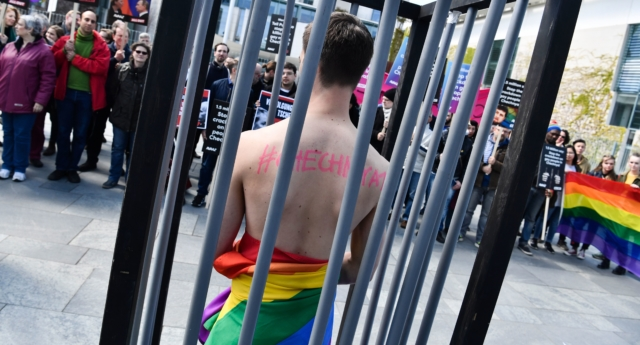 An activist stands naked, wrapped in a rainbow flag, in a mock cage in front of the Chancellery in Berlin on April 30, 2017, during a demonstration calling on Russian President to put an end to the persecution of gay men in Chechnya.  (JOHN MACDOUGALL/AFP/Getty)