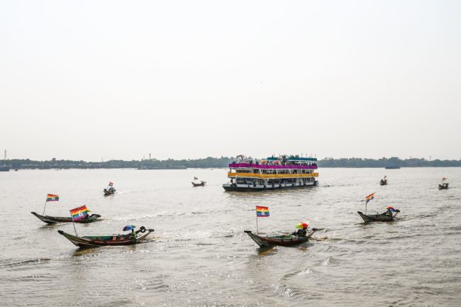 Wooden boats displaying lesbian, gay, bisexual, and transgender (LGBT) community flags float near the jetty during the Pride Boat Parade, an event of the Myanmar's Yangon Pride festival.
