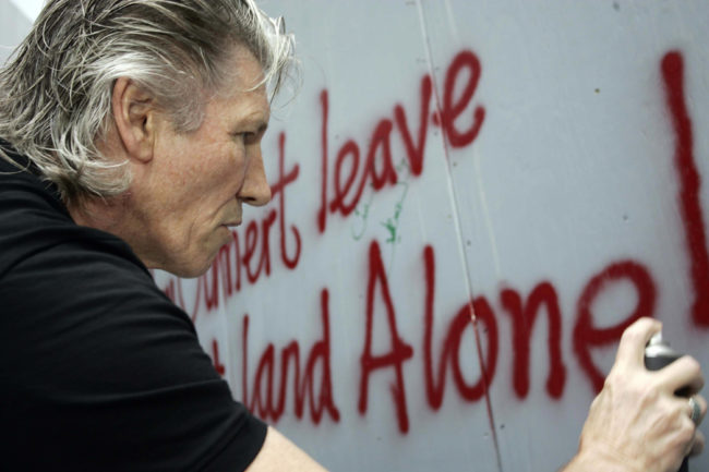 British rock legend Roger Waters, one of the signatories of a letter demanding the BBC opposed Israel hosting Eurovision, spraypaints a graffiti against Israel?s separation barrier surrounding the West Bank town of Bethlehem.