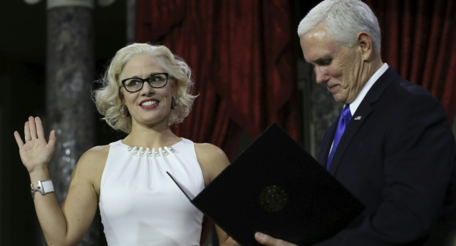 US Senator from Arizona Kirsten Sinema holds a law book as she is sworn in by Vice President Mike Pence on January 3, 2019.