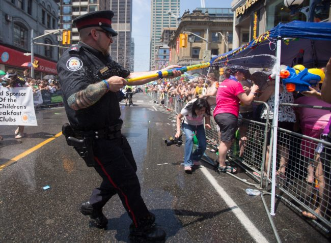 A Toronto Police Officer fires a water gun at spectators at Pride Toronto in 2014.