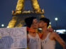 "Young people in favor of same sex marriage  kisses each other and hold a board reading in French ""Free to love"" in front of the Eiffel Tower, to protest at the end of a march against same-sex marriage on January 13, 2013 in Paris. MIGUEL MEDINA/AFP/Getty)"