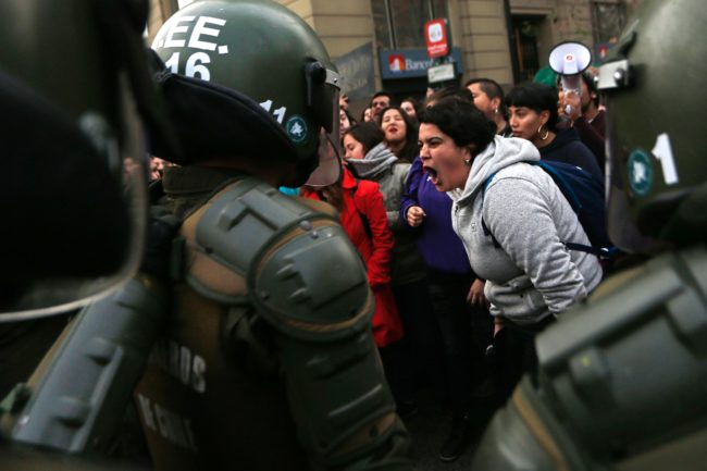 "Pro-choice and gay, lesbian, bisexual and trans activists argue with riot police as the bus chartered by ""Hazte Oir"" (Make yourself heard) conservative association passes by La Moneda presidential palece in Santiago in 2017, the same year the girl was allegedly raped"