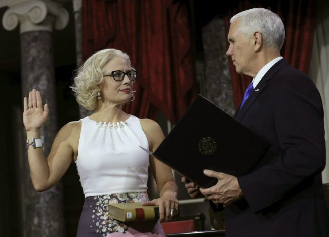 US Senator from Arizona (D) Kyrsten Sinema holds a lawbook as she is sworn in by Vice President Mike Pence (R) during the swearing-in re-enactments for recently elected senators in the Old Senate Chamber on Capitol Hill January 3, 2019