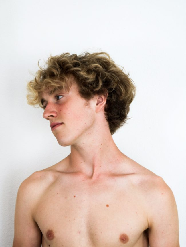 A naked man against a white background, looking to the side