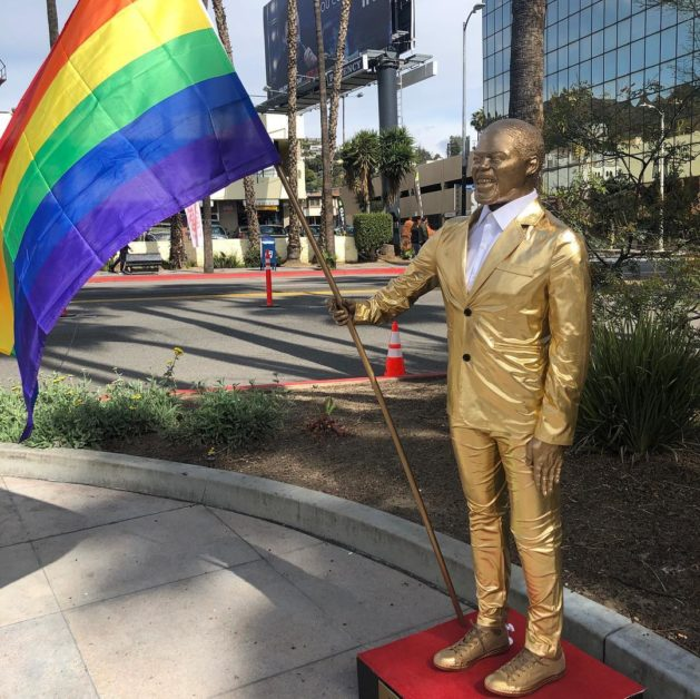 The Kevin Hart statue holds a rainbow flag. (Plastic Jesus/Instagram)