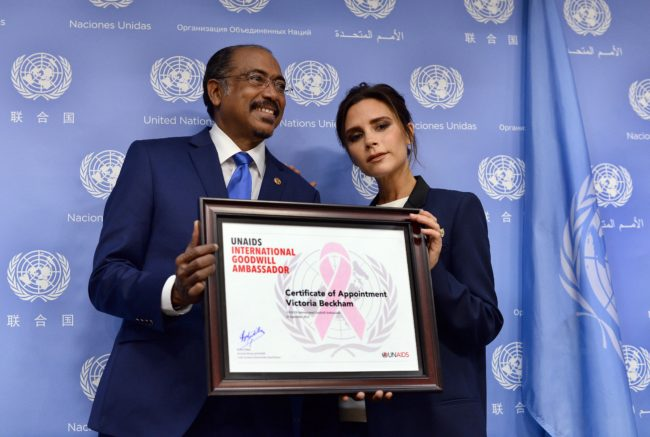 Executive Director of Joint UN Programme on HIV/AIDS Michel Sidibe (L) presents British fashion designer Victoria Beckham with a UNAIDS international goodwill ambassador certificate during a press conference on the sideline of the 69th Session of the UN General Assembly at the United Nations in New York on September