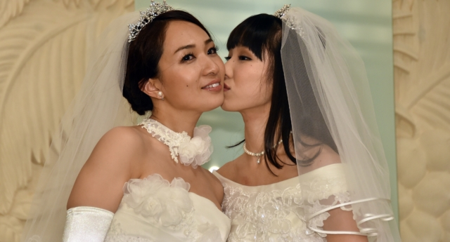 Japanese actress Akane Sugimori (R) kisses her partner Ayaka Ichinose in a symbolic wedding ceremony in Tokyo in 2015— Calls for Japan to legalise same-sex marriage are growing, with 13 gay couple sfiling a lawsuit on Valentine's Day.  (Yoshikazu Tsuno/AFP/Getty)