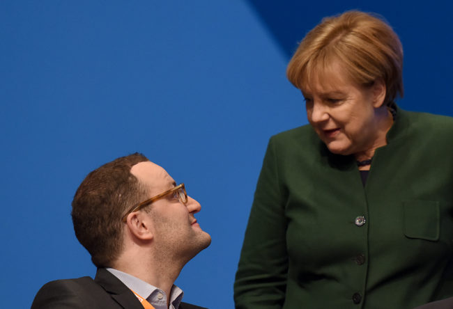 Chancellor of Germany Angela Merkel speaks with the Member of the German Parliament, Jens Spahn during the 29th annual congress of the Christian Democrats (CDU) on December 7, 2016 in Essen, Germany.