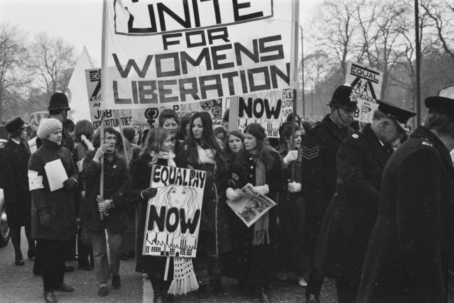 Members of the National Women's Liberation Movement, on an equal rights march from Speaker's Corner to No.10 Downing Street, to mark International Women's Day, London, 6th March 1971. One woman is carrying a placard reading 'Equal Pay Now'. On the right, a woman is holding a copy of the Trotskyist publication 'Red Mole'.