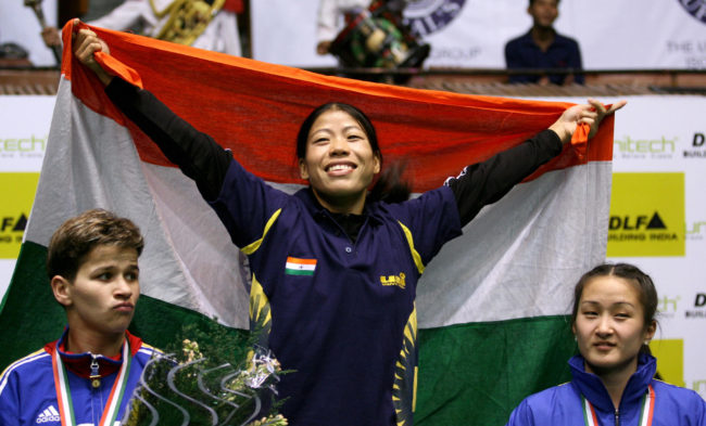 Indian boxer MC Mary Kom (C) is watched by silver medalist Steluta Duta (L) of Romania and bronze medalist Jong OK (R) of North Korea as she celebrates during prize ceremony, after winning a gold medal at the fourth World Women's Boxing Championship in New Delhi, 23 November 2006. India won four gold medals at the Championships which took place in the Indian capital from 18-23 November.