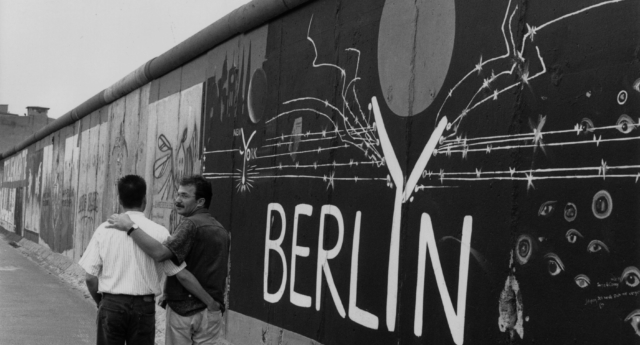 A gay couple strolling past the graffiti on a remaining section of the Berlin Wall, August 1993. (Steve Eason/Hulton Archive/Getty)