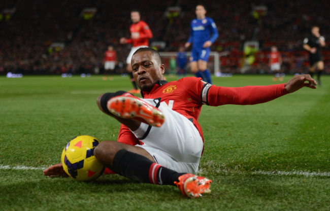 Patrice Evra of Manchester United tries to keep the ball in play during the Barclays Premier League match between Manchester United and Cardiff City at Old Trafford on January 28, 2014 in Manchester, England.